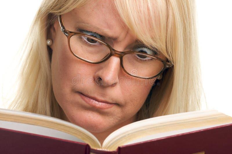 O Blonde confuso lê um livro imagem de stock royalty free