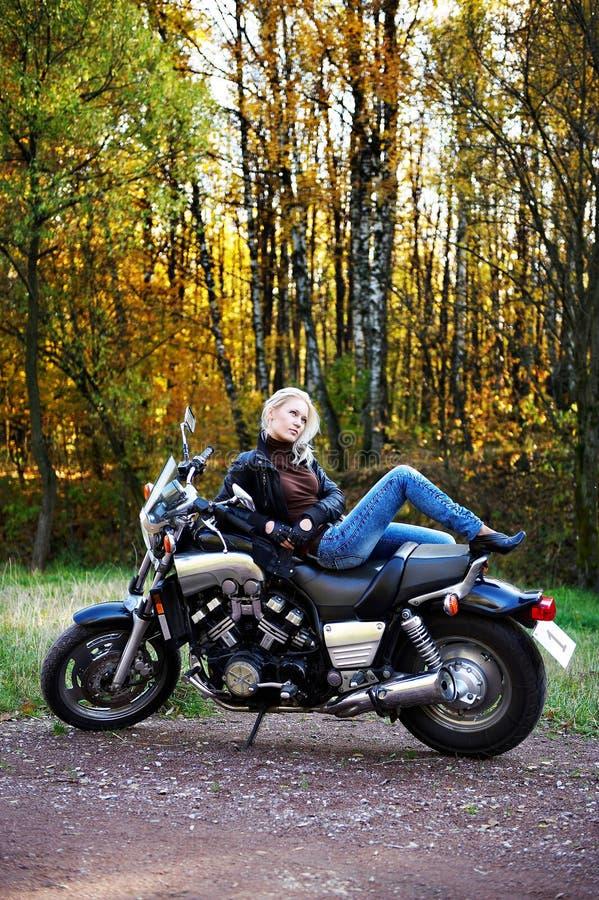 O blonde encontra-se na motocicleta grande imagem de stock