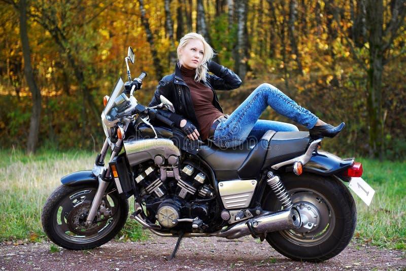O blonde encontra-se na motocicleta grande fotografia de stock