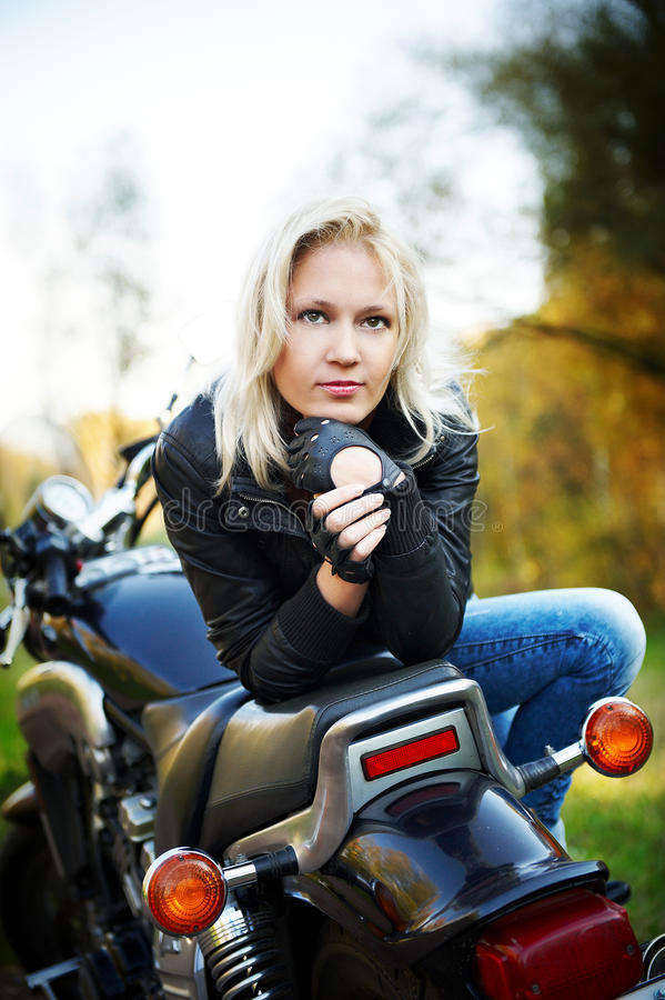 O blonde senta-se na motocicleta foto de stock