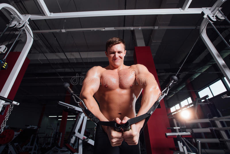 O bodybuider forte grande sem camisas demonstra exercícios do cruzamento Os músculos peitorais e o treinamento duro imagem de stock
