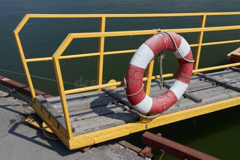 O boia salva-vidas pendura nos trilhos da ponte transitória fotos de stock