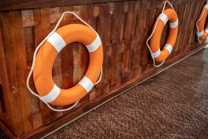 O boia salva-vidas soa a suspensão no assoalho de madeira de painel e de tapete de parede foto de stock