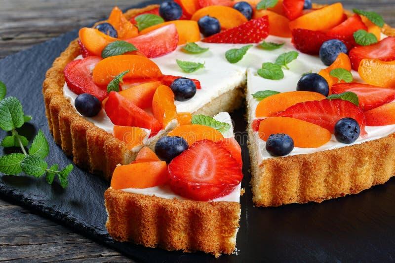 O bolo cobriu com morangos, mirtilos, hortelã foto de stock