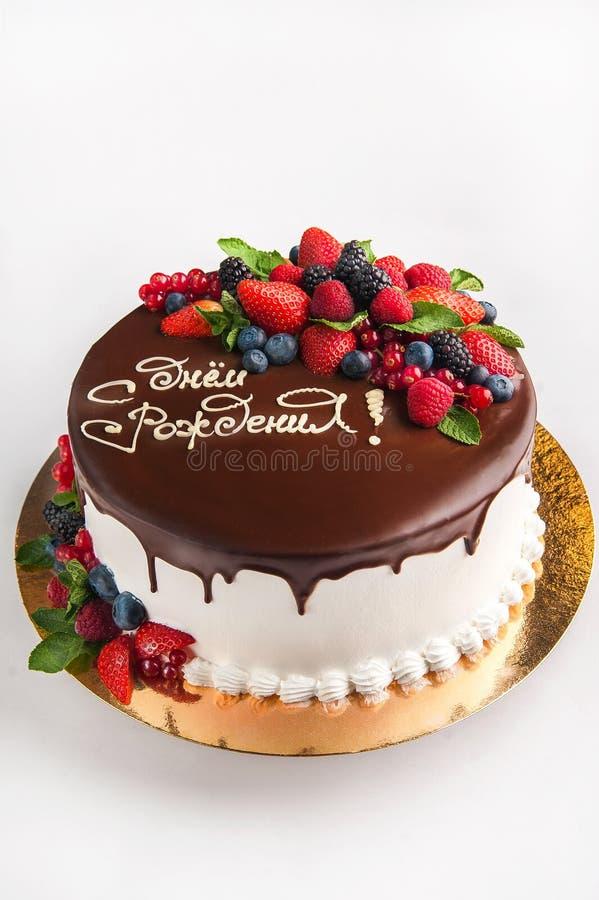 O bolo com fruto, chocolate, flores é isolado em um espaço branco do close-up e da cópia do fundo No russo a inscrição 'B feliz fotos de stock royalty free