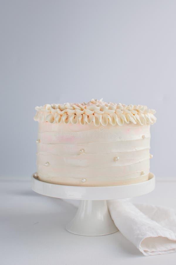 O bolo de aniversário bonito decora com as pérolas comestíveis no fundo neutro branco fotos de stock