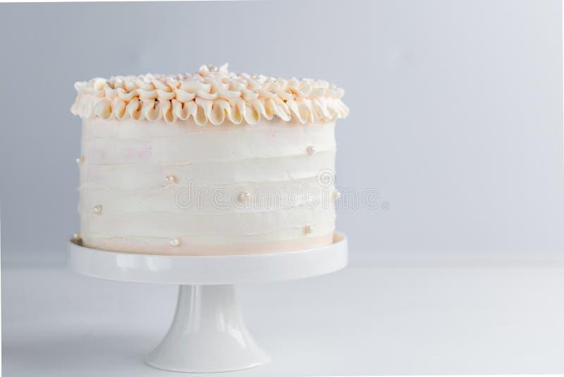 O bolo de aniversário bonito decora com as pérolas comestíveis no fundo neutro branco Copie o espaço Conceito da celebração Camad fotografia de stock royalty free