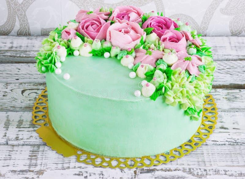 O bolo de aniversário com flores aumentou no fundo branco foto de stock