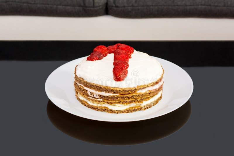 O bolo de aniversário doce com morangos e numera um em uma placa branca imagem de stock royalty free