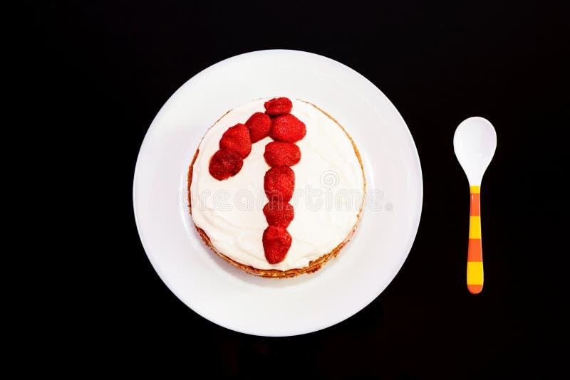 O bolo de aniversário doce com morangos e numera um em uma placa branca foto de stock