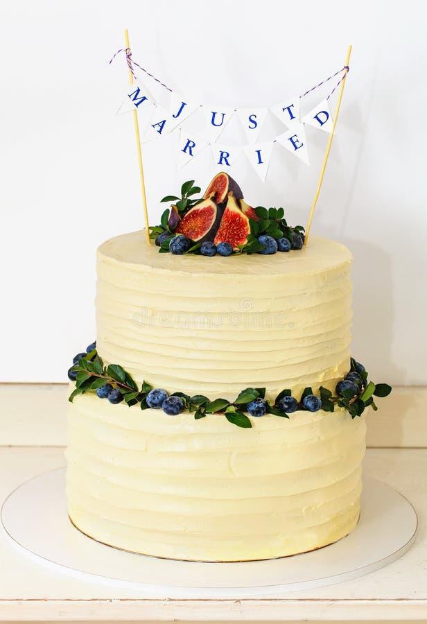 O bolo de casamento cobriu com o figo no fundo branco fotografia de stock royalty free