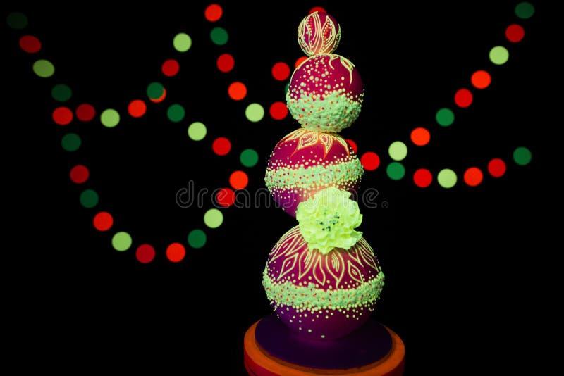 O bolo de casamento colorido brilhante da fotografia UV de néon incandesce cores fluorescentes em um fundo escuro nos raios de imagens de stock
