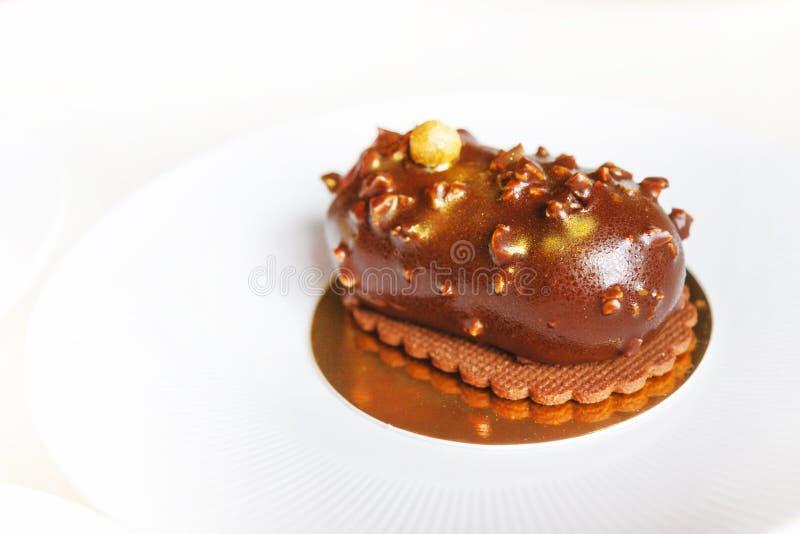 O bolo de chocolate é polvilhado com o ouro comestível em uma placa branca imagens de stock