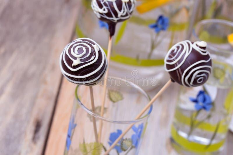 O bolo de chocolate estala nas varas no vidro, de madeira imagem de stock royalty free