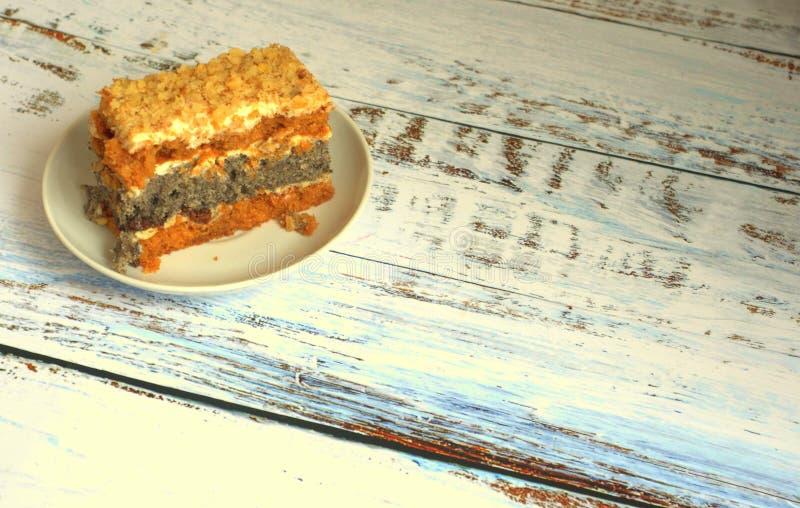 O bolo de esponja com as sementes de papoila em uma placa encontra-se em uma tabela de madeira imagem de stock