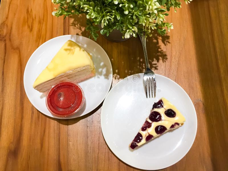 O bolo de queijo do mirtilo e o bolo do crepe com molho da morango estão no prato branco, há uma árvore pequena no potenciômetro  imagens de stock