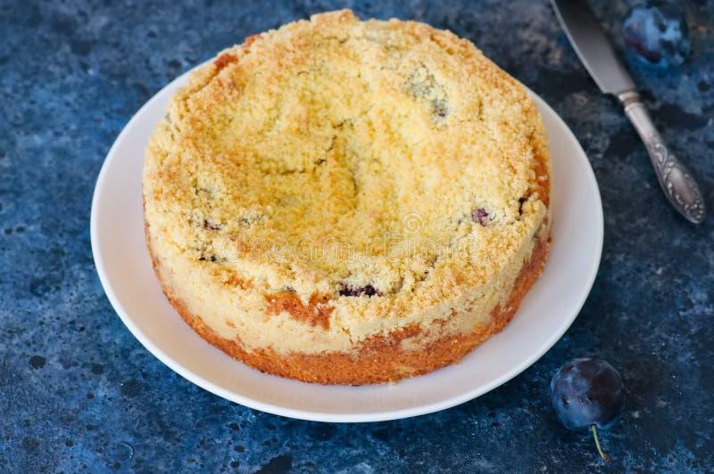 O bolo do crumble da farinha de milho com enchimento do doce da ameixa serviu em um branco imagem de stock royalty free