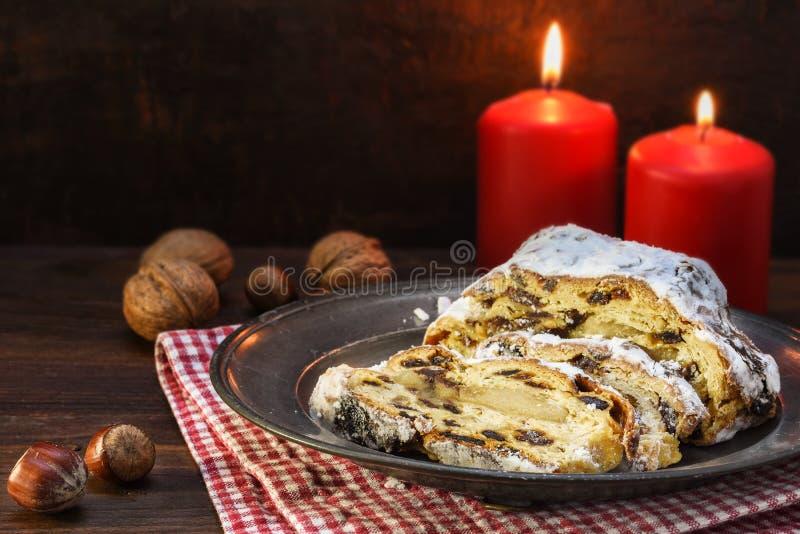 O bolo do Natal, alemão christstollen com frutos, passas e maçapão na frente de duas velas e porcas vermelhas na madeira escura r fotos de stock royalty free