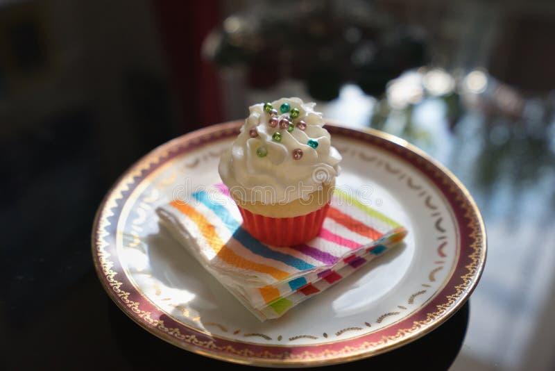 O bolo do queque ou do copo com chantiliy e colorfull pequeno adoça os perigos servidos na placa de sobremesa pequena com guardan fotografia de stock royalty free