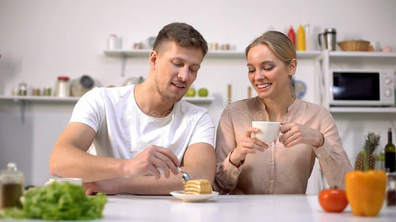 O bolo doce comer masculino, chá bebendo da amiga alegre tem o café da manhã junto fotografia de stock royalty free