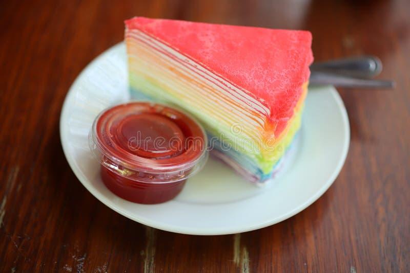 O bolo macio do crepe, a cor bonita, com molho do chantiliy e da framboesa vermelha puseram placas e utensílios imagem de stock