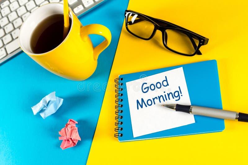 O bom dia - é escrito no bloco de notas pequeno com um copo do café da manhã no fundo de madeira rústico com baixa cena chave imagem de stock