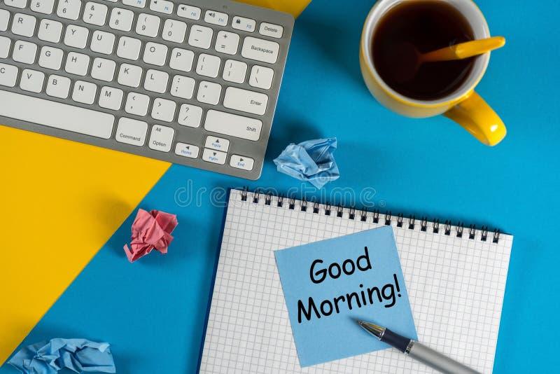 O bom dia - é escrito no bloco de notas pequeno com uma xícara de café, a pena, o teclado no local de trabalho brilhante no escri foto de stock