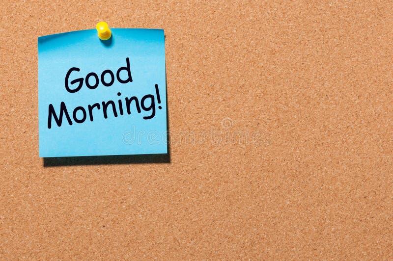O bom dia deseja na nota fixada no corkboard do escritório com espaço vazio para o texto, o modelo ou o molde foto de stock