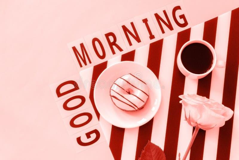 O bom dia do texto, café, filhós, aumentou flor no guardanapo e no fundo cor-de-rosa Local de trabalho à moda colocado plano do c imagens de stock