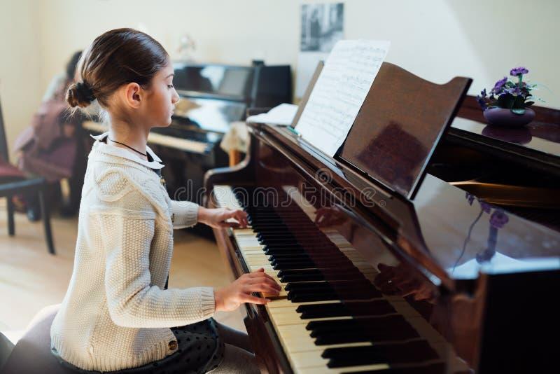 O bom estudante joga o piano em uma escola de música fotografia de stock