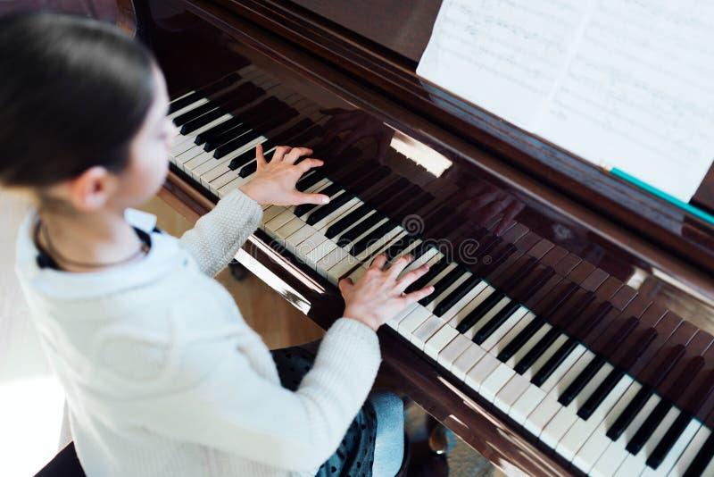 O bom estudante joga o piano em uma escola de música imagens de stock