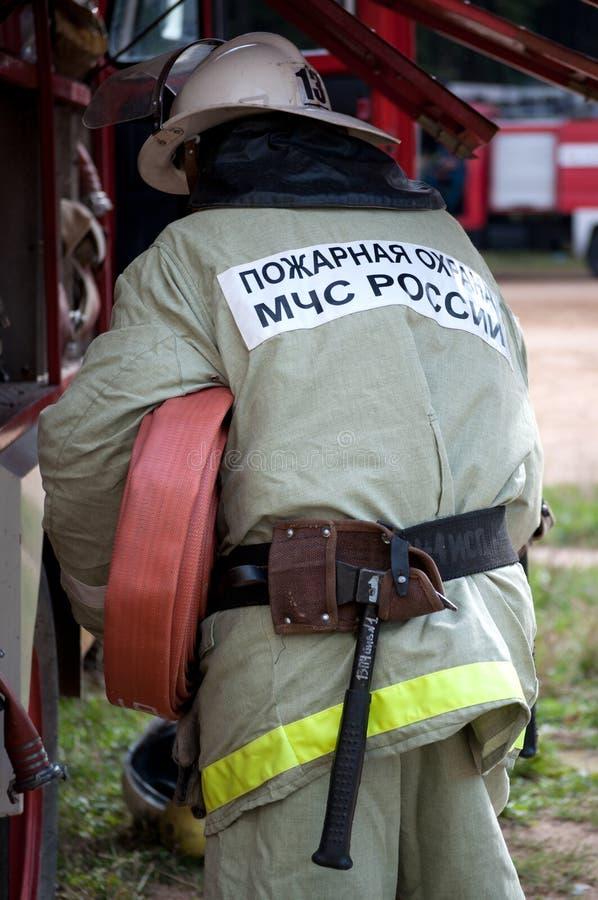 O bombeiro retira a mangueira de fogo do carro fotos de stock royalty free