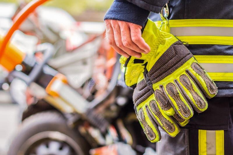 O bombeiro trabalha com ferramentas profissionais em um carro deixado de funcionar fotos de stock