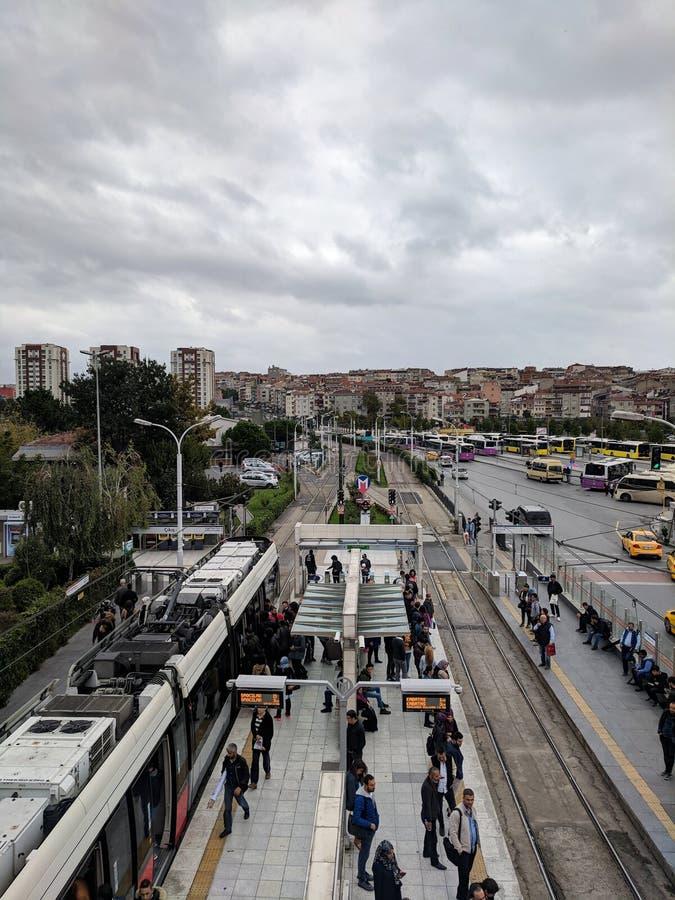 O bonde chega na estação de metro de Zeytinburnu Opinião de ângulo alto de cima na junção da multidão e de estrada dos povos imagens de stock royalty free
