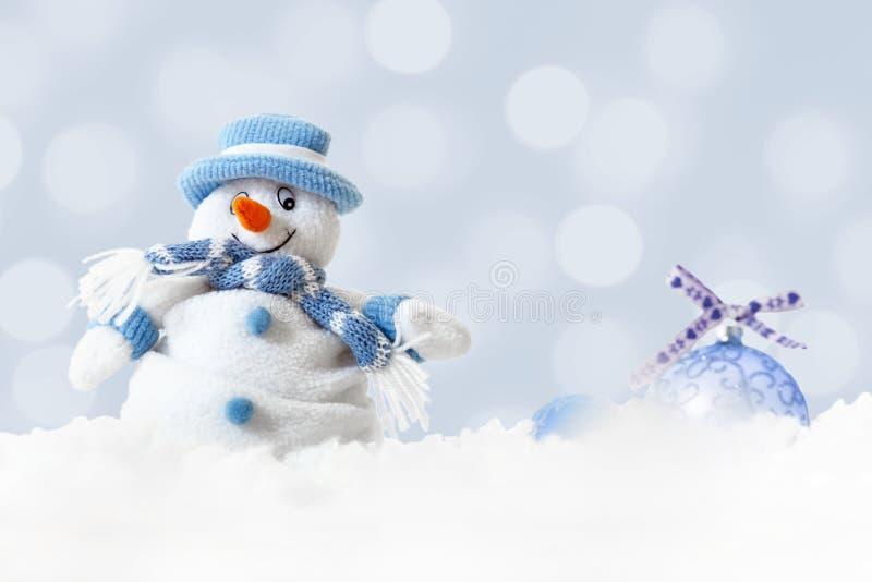 O boneco de neve azul engraçado no xmas ilumina o fundo do bokeh, os flocos de neve brancos, o Feliz Natal e o conceito do cartão imagens de stock royalty free