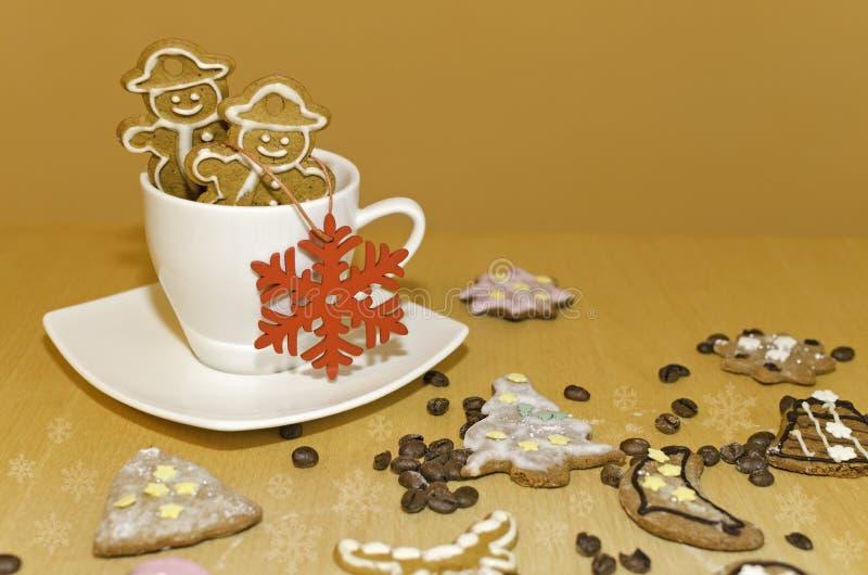 O boneco de neve do Natal deu forma a pão-de-espécie em um copo de café fotos de stock