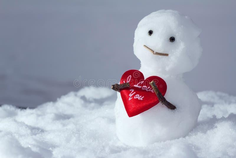 O boneco de neve engraçado prende um coração imagens de stock
