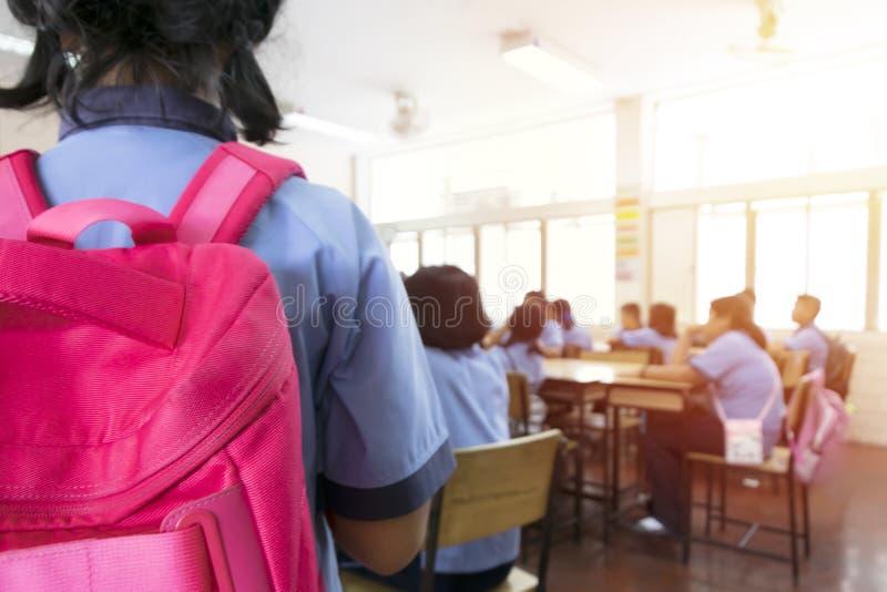 O borrão da sala de aula, menina com a trouxa vermelha que vem ao classroo fotografia de stock royalty free
