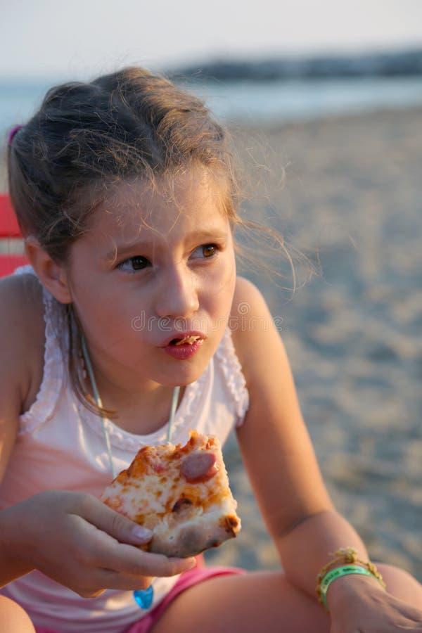 O borracho bonito come uma fatia de pizza na praia imagens de stock