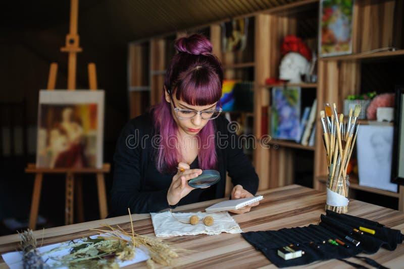 O botânico da jovem mulher analisa uma flor secada fotografia de stock royalty free