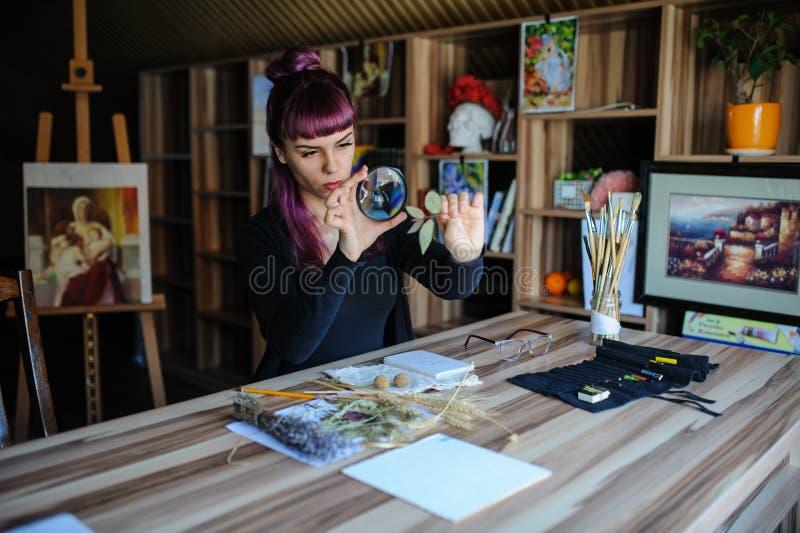 O botânico da jovem mulher analisa uma flor secada fotos de stock