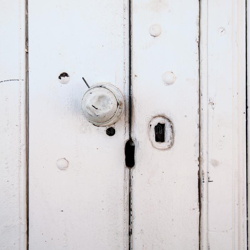 O botão de porta amolgado em um velho pintou a porta de madeira imagens de stock