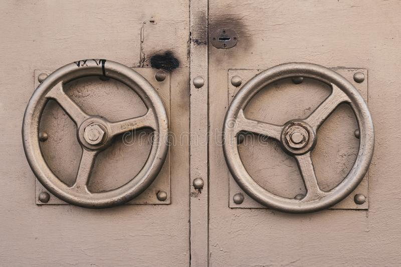 O botão de porta metálico na forma do volante dourado Cor dourada da porta velha com os dois punhos redondos da porta imagem de stock royalty free