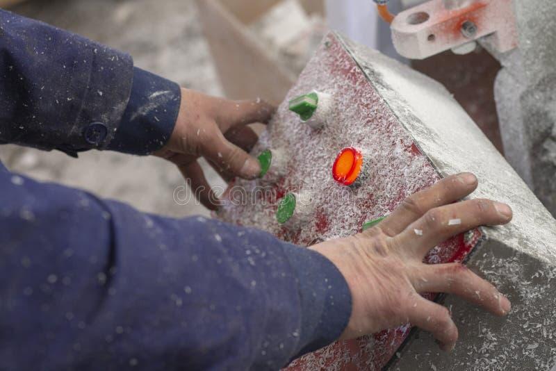 O botão do controle na fábrica, o botão vermelho é iluminado, a pessoa atrás do equipamento imagens de stock