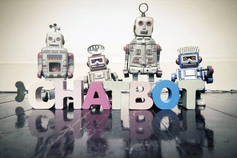 O BOT da palavra BATE-PAPO com letras de madeira e os robôs retros do brinquedo sobre foto de stock royalty free