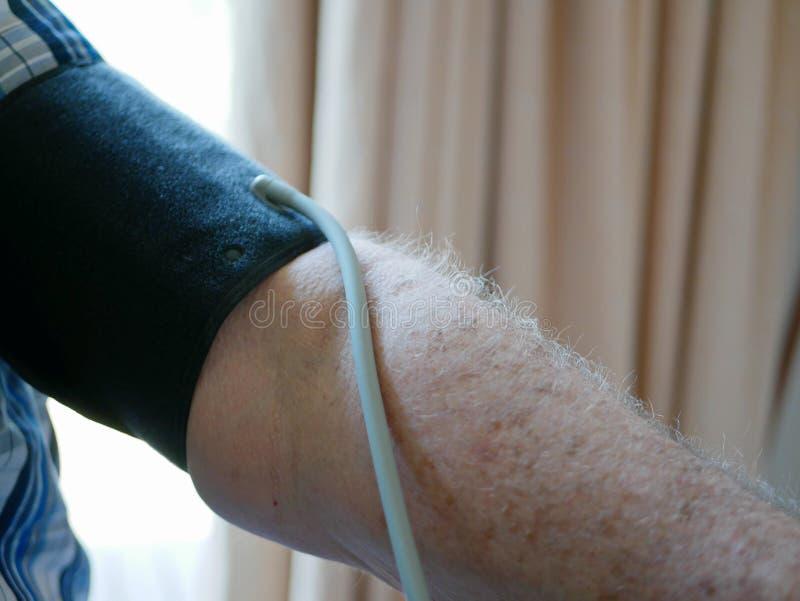 O braço de um ancião com um punho da pressão em verificar sua pressão sanguínea em casa só foto de stock