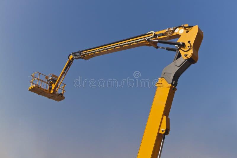 O braço e a plataforma da máquina desbastadora amarela fotografia de stock