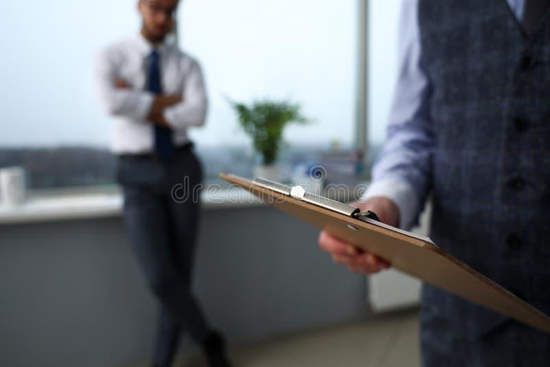 O braço masculino do caixeiro no terno e o laço com papel grampearam para acolchoar imagens de stock royalty free
