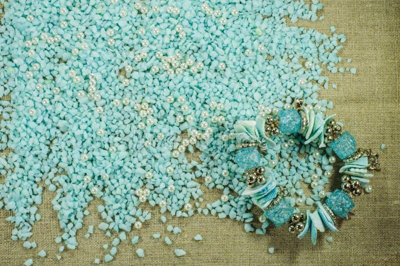 O bracelete azul com shell no cascalho azul dispersado com pérola perla fotografia de stock