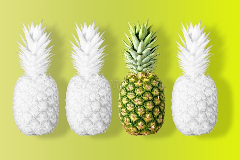 O branco coloriu abacaxis em um fundo amarelo vívido foto de stock royalty free